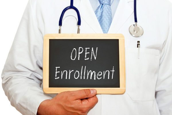 a doctor holding a sign saying open enrollment