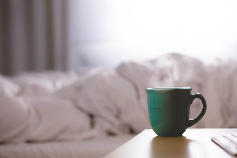 a cup of tea by a bed